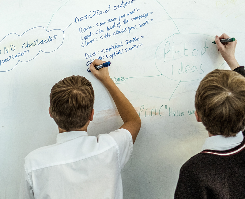 Students writing code on a whiteboard
